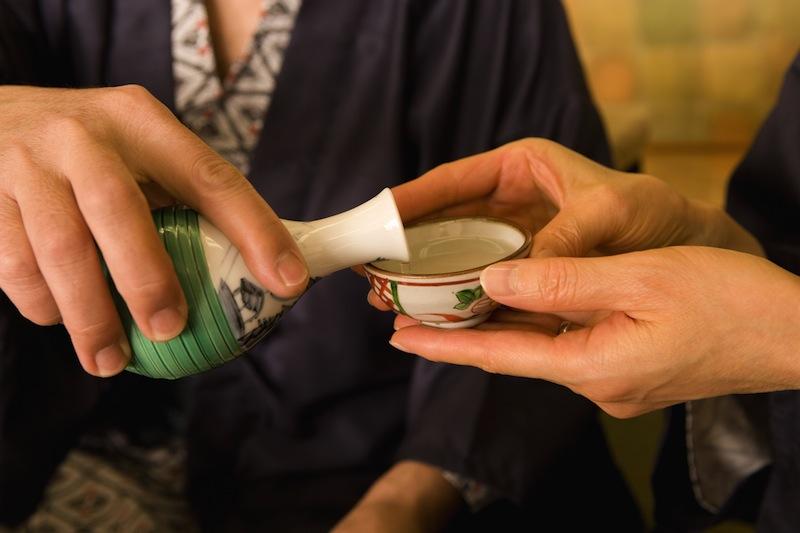 親に日本酒を注ぐ息子